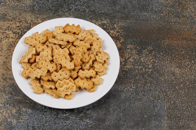 Set van zoute crackers op witte plaat.