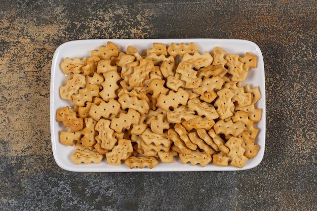 Set van zoute crackers op witte vierkante plaat.