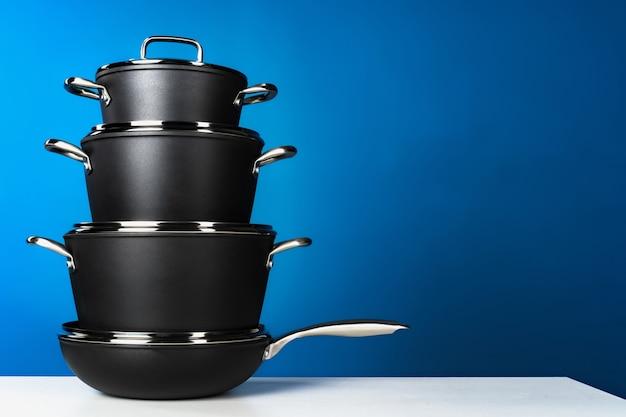 Set van zwart kookgerei tegen blauwe achtergrond vooraanzicht