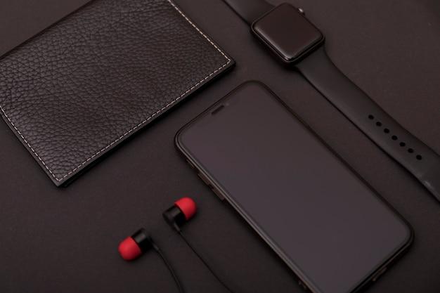 Set van zwart lederen portemonnee, smartwatch, smartphone en oortelefoons.