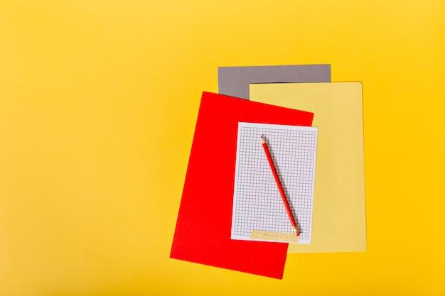 Set veelkleurig papier en rood potlood op oranje muur