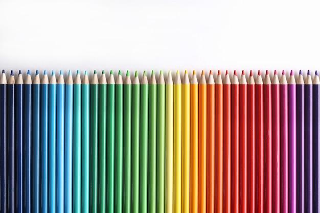 Set veelkleurige potloden liggend op een witte ondergrond