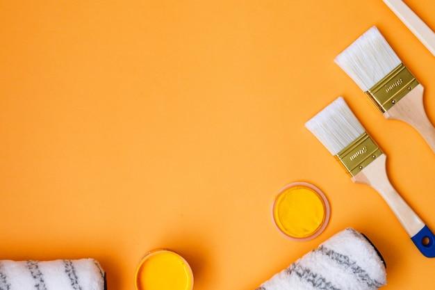 Set verfborstels met verf op een oranje achtergrond