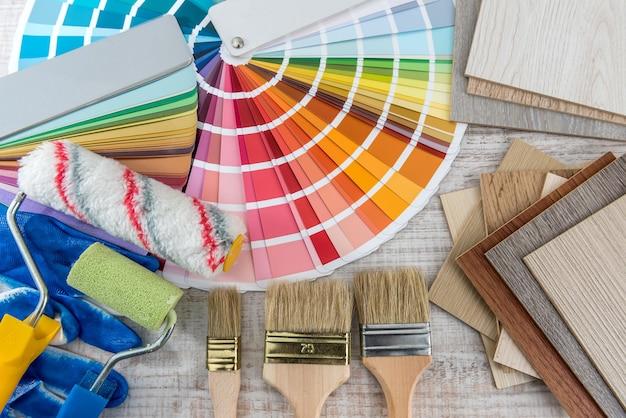 Set verfgereedschappen als paletgids voor kleurenpapier, blauwe handschoenen en penseel op een houten bord. bouw- en renovatieconcept