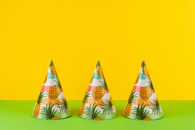 Set verjaardagsfeestje hoeden op een rij met ananas op gele en groene achtergrond. kopieer ruimte. gelukkige verjaardag of vakantie exotische concept.