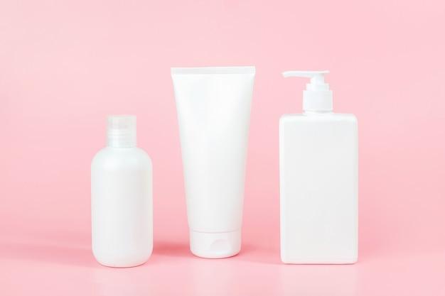 Set verzorgingscosmetica voor huid, lichaam of haar. drie witte lege cosmetica flessen op roze