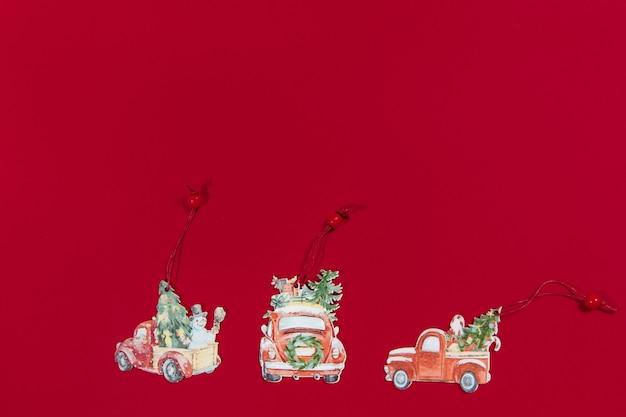 Set vintage kerst houten speelgoedauto's op kerstboom op rode achtergrond