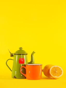 Set vintage theekopje, oranje beker en citroen. kopieer de ruimte bovenaan