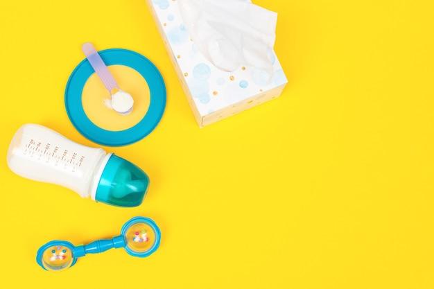 Set voedingsaccessoires voor baby-baby. babyvoeding concept. zuigfles met melk, servet, lepel met formule en zitzak op een gele achtergrond