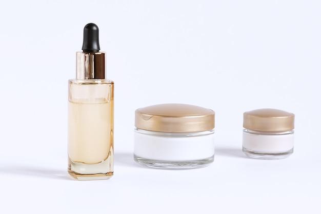 Set voor de verzorging van de huid rond de ogen en de huid bestaande uit glazen potjes crème en een flesje met een serumpipet