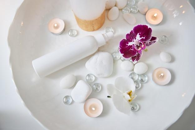 Set voor spa-procedure met orchideeën en fles lotion