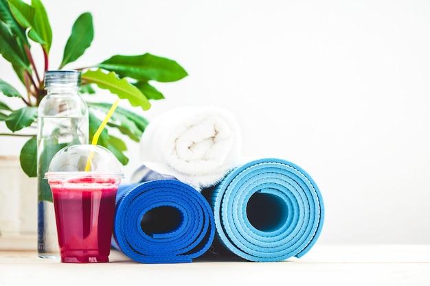 Set voor sport, een yogamat, een handdoek, smoothies, fles water, gezonde levensstijl