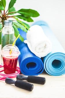 Set voor sport, een yogamat, een handdoek, smoothies, springtouw, een fles water