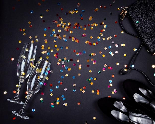 Set vrouwen accessoires voor feest en gouden kleurrijke confetti op zwart oppervlak