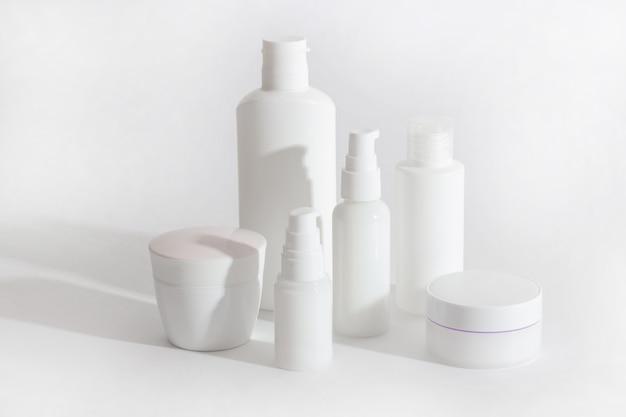 Set witte cosmetische flessen en potten met harde schaduwen. thuis- en schoonheidssalon zorgconcept