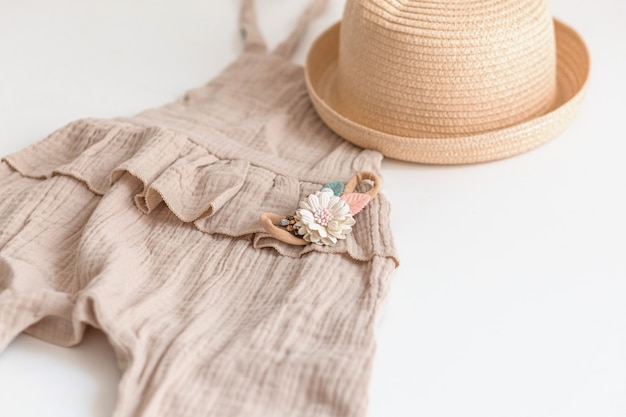 Set zomer kinderkleding voor meisjes, stijlvol rompertje, strohoed en bloemenaccessoire.