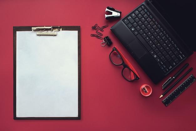 Set zwarte briefpapier elementen met plastic tablet en wit vel papier op de rode achtergrond. bovenaanzicht. concept van nieuwe kansen, ideeën, ondernemingen, innovaties.
