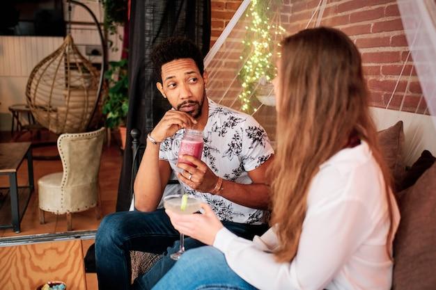 Sex tussen verschillendre rassen paar verliefd drinken van een cocktail in een exclusieve bar