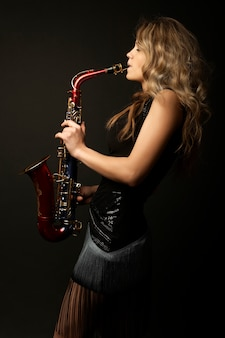 Sexy aantrekkelijk blondevrouwenmodel met saxofoon