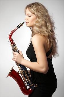 Sexy aantrekkelijke blondevrouwen met saxofoon