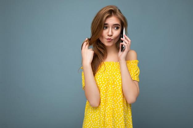 Sexy aantrekkelijke positieve lachende jonge blonde vrouw, gekleed in stijlvolle gele zomerjurk permanent geïsoleerd over blauwe achtergrond houden en praten op mobiele telefoon op zoek naar de kant.