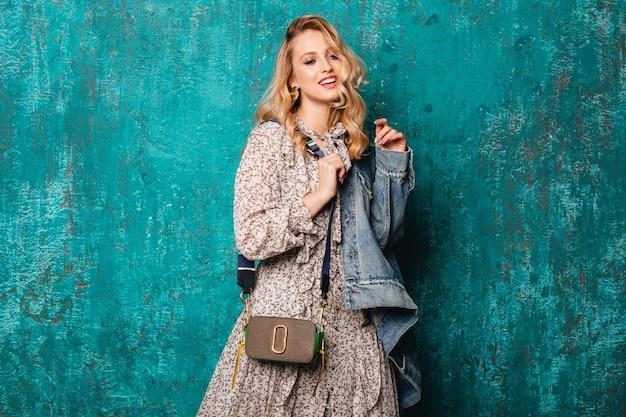 Sexy aantrekkelijke stijlvolle blonde vrouw in spijkerbroek en oversized jas lopen tegen vintage groene muur in straat