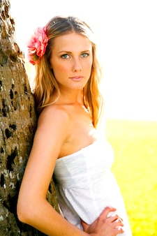 Sexy, aantrekkelijke vrouw in een vrouwelijke jurk leunt tegen de boomstam