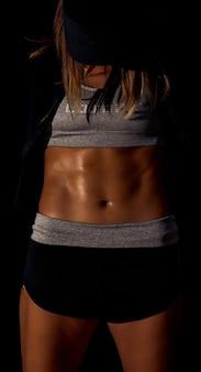 Sexy atletische vrouw die spieren oppompt, mooi fitnessmodel in donkere studio terwijl ze bedekt is met zweet