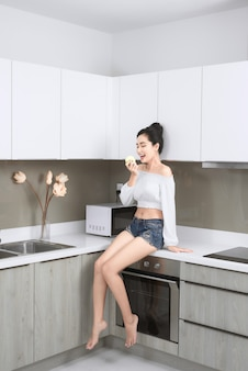 Sexy aziatische vrouw die appel eet terwijl ze in de keuken zit.