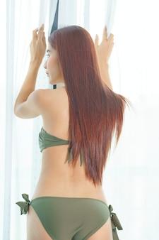 Sexy aziatische vrouw in bikini groen op de slaapkamer in de vakantie