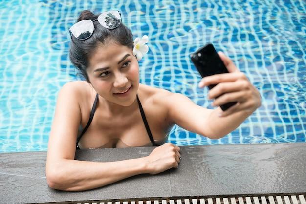 Sexy aziatische vrouw selfie in zwembad