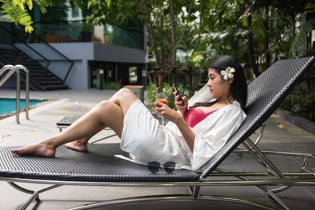 Sexy aziatische vrouw spelen smartphone en drinken sap
