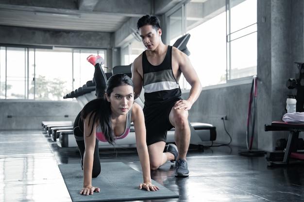 Sexy aziatische vrouw training lagere dij op een yoga mat met trainer man in de sportschool. concept van oefening in de sportschool. vrouw en man trainen op yogamat.