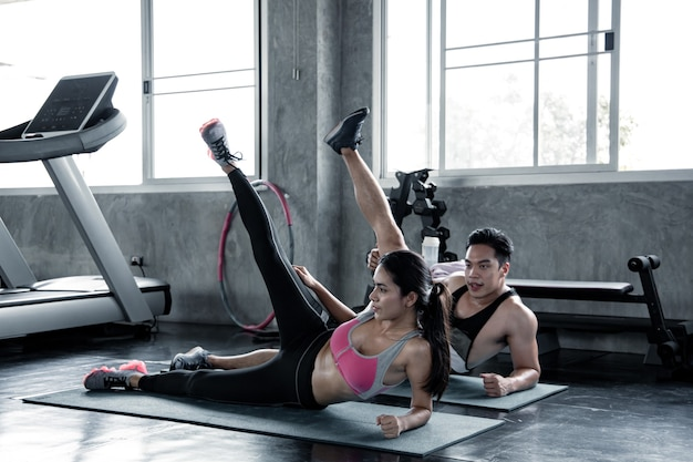 Sexy aziatische vrouw training lagere dij op een yoga mat met trainer man in de sportschool. concept van oefening in de sportschool. vrouw en man training op yogamat.