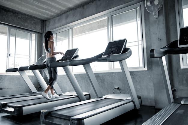 Sexy aziatische vrouwen die op de lopende machine in de gymnastiek uitoefenen. vrouw training in de sportschool gezond. concept van gezondheidszorg met oefening in de sportschool. mooi meisje fitness in de sportschool spelen.