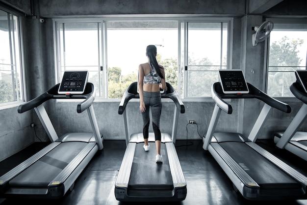 Sexy aziatische vrouwen die op de lopende machine in de gymnastiek uitoefenen.