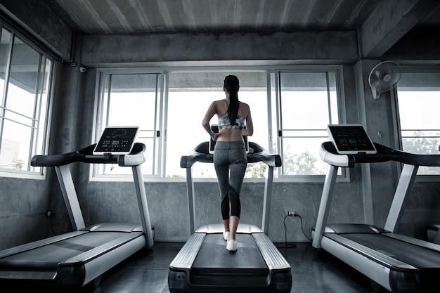 Sexy aziatische vrouwen oefenen op de lopende machine in de sportschool. vrouw training in sportschool gezond. concept van gezondheidszorg met oefening in de sportschool. mooi meisje fitness spelen in de sportschool.