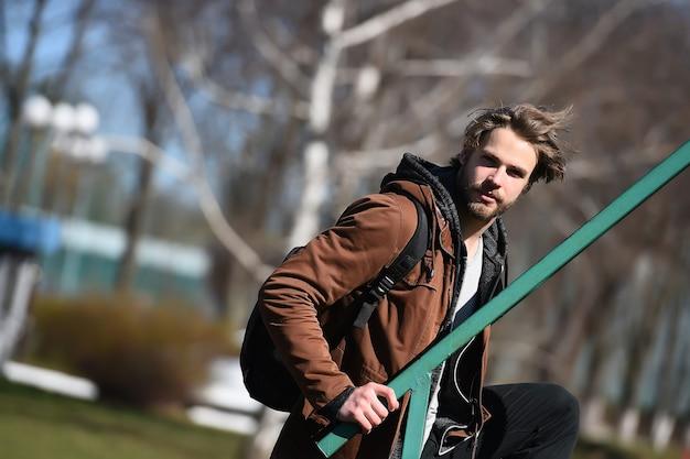 Sexy bebaarde man of knappe jongen in bruine hoodie jas of trui met sporttas, heeft stijlvol haar zonnig buiten op onscherpe achtergrond bij trapleuning, kopieer ruimte