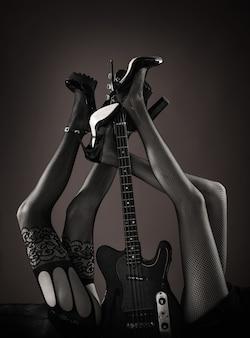 Sexy benen. fetish, sexy vrouw, elektrische gitaar en benen, ondergoed. fetisj lingerie. gitaar, elektrische gitaar. muziekfestival, live muziek, concert. instrument op het podium en band. muziekconcept.