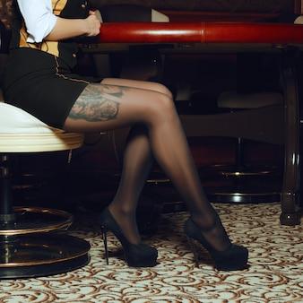 Sexy benen van casinogroep croupier in leunstoel