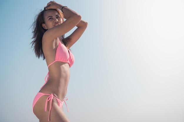 Sexy bikini lichaam vrouw zonnebril ontspannen op perfect tropisch strand en turkoois oceaan water. onherkenbaar model in mode zwemkleding met gladde bruine huid.