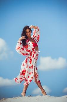 Sexy bikinilichaam vrouw die zich vrij voelt met een slanke buik en gladde dijen, gekleed in kleurrijke mode sjaal rok badmode strandkleding die pronkt met gewichtsverlies. laser beauty spa wellness-concept.