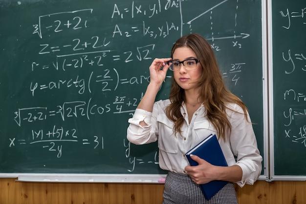 Sexy blanke vrouwelijke leraar tegen bord met wiskundige formules in de klas. opleiding. school