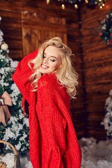 Sexy blond meisje in de rode trui, plezier maken
