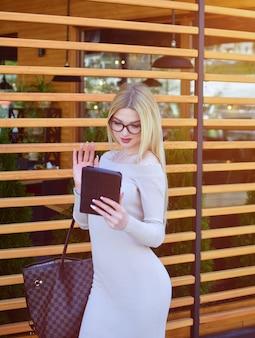 Sexy blond meisje praten over video-oproep op tablet. een aantrekkelijk model in zonnebril en een jurk maakt gebruik van een tablet.