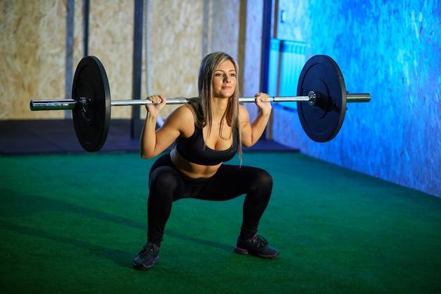 Sexy blonde atletische vrouw in een zwarte strakke beenkappen die met een barbell in de gymnastiek uitoefenen