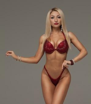 Sexy blonde bodybuildervrouw in bikini op grijze achtergrond