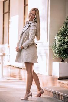 Sexy blonde in beige lingerie en jas poseren in de buurt van het café. rust en genot.