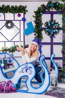 Sexy blonde in blauwe kerstmuts van de kerstman zittend op ch