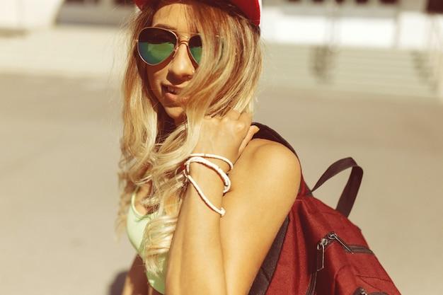 Sexy blonde jonge vrouw die op de straat loopt